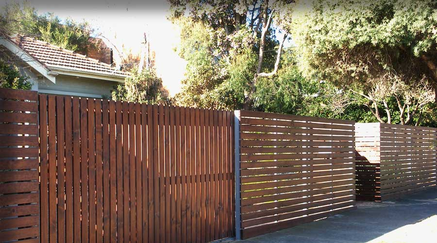 Fence includes Straight Top Configuration combining horizontal & wider Vertical Slats with Automated Sliding Gate fixed to a galvanized steel frame